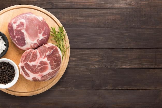 Odgórnego widoku wieprzowiny kotlecika surowy stek i czosnek, pieprz na drewnianym tle. skopiuj miejsce na tekst