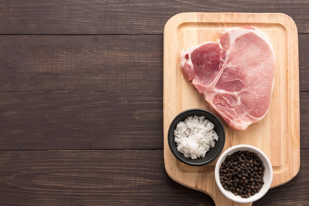 Odgórnego widoku wieprzowiny kotlecika surowy stek i sól, pieprz na drewnianym tle