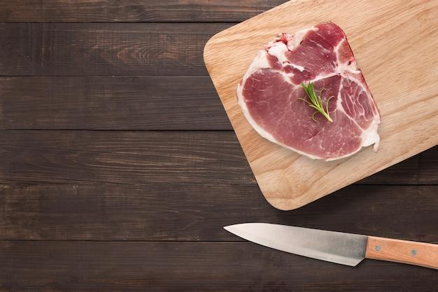 Odgórnego widoku wieprzowiny kotlecika surowy stek na tnącej desce i nóż na drewnianym tle. copyspace dla tekstu