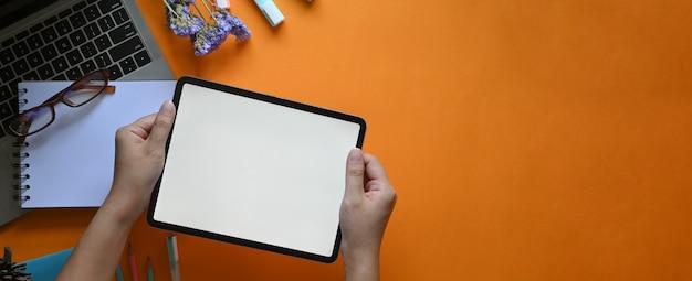 Odgórnego widoku wizerunek kreatywnie kobiet ręki trzyma białą pustego ekranu komputerową pastylkę nad komputerowym laptopem, szkłami, markierów piórami, ołówkami, notatnikiem i kwiatami, który stawia na kolorowym pracującym biurku.