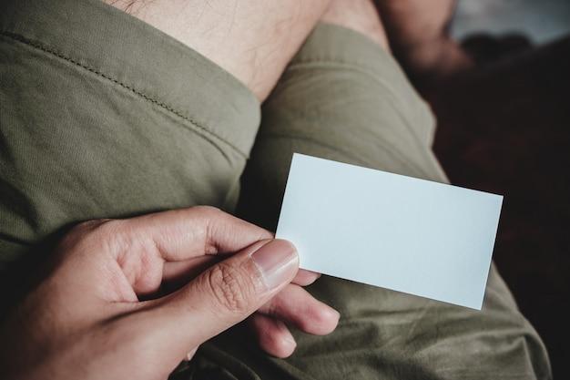 Odgórnego widoku wizerunek mężczyzna ręki mienia pusta wizytówka podczas gdy siedzący w kawiarni
