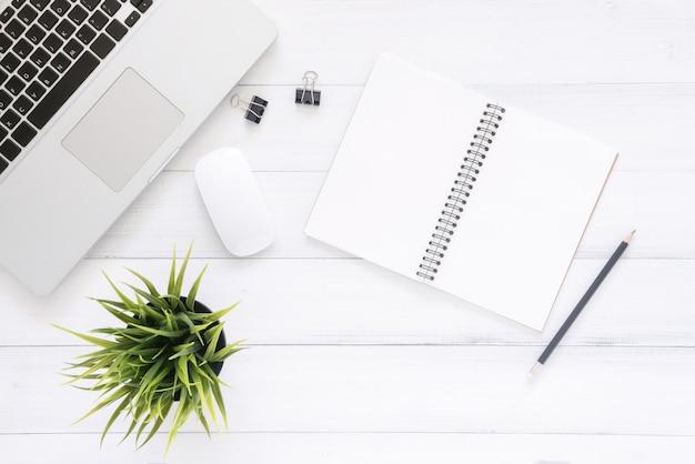 Odgórnego widoku wizerunek otwarty notatnik z pustymi stronami i laptopem na drewnianym stole
