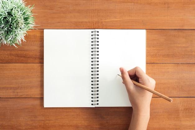 Odgórnego widoku wizerunek otwarty notatnik z pustymi stronami na drewnianym stole. gotowy do dodania tekstu lub makiety