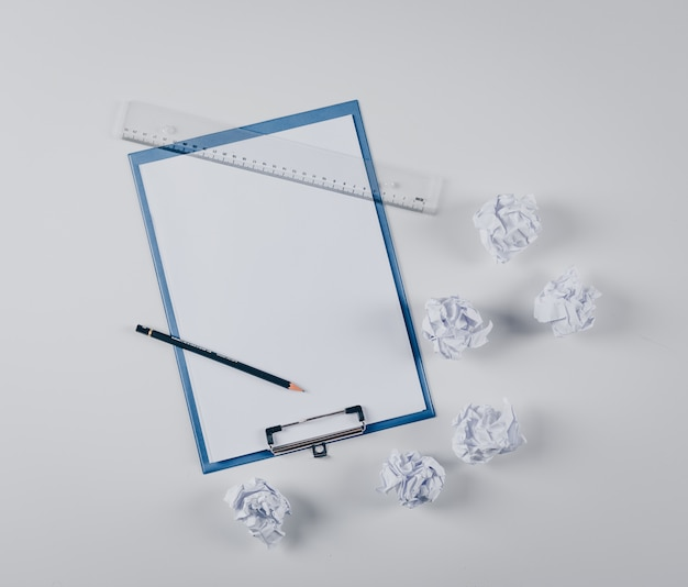 Odgórnego widoku władca i ołówek w schowku z zmiętymi papierami na bielu
