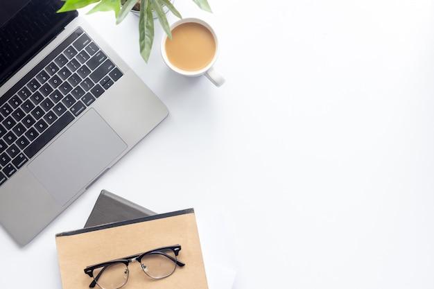 Odgórnego widoku workspace laptop na bielu stole z filiżanką i notatnikiem na tle