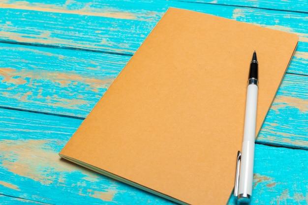 Odgórnego widoku workspace z pustym notatnikiem i piórem na drewnianym stołowym tle