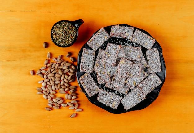 Odgórnego widoku zachwyta tureccy lokums w talerzu z pistacją na żółtym drewnianym tle. poziomy
