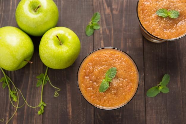 Odgórnego widoku zieleni jabłek smoothie na drewnianym tle