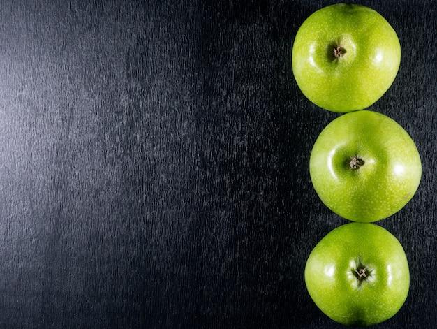 Odgórnego widoku zieleni jabłka z kopii przestrzenią na lewicie na czarny drewniany horyzontalnym