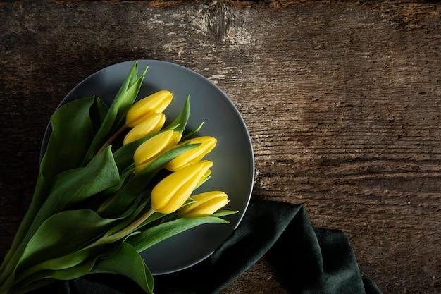 Odgórnego widoku żółci tulipany na talerzu
