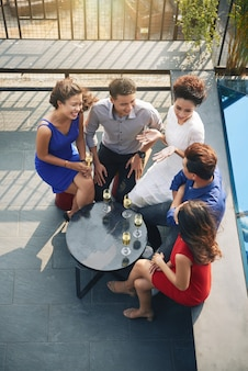 Odgórny strzał grupa przyjaciele jest usytuowanym atound stół przy plenerowym przyjęciem