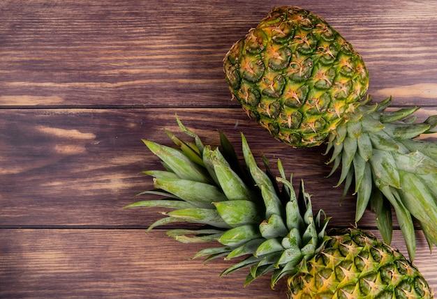 Odgórny widok ananasy na prawej stronie i drewniany tło z kopii przestrzenią