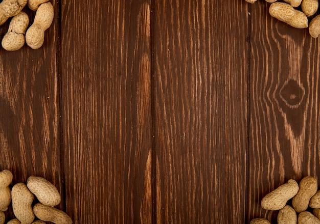 Odgórny widok arachidy w skorupie rozpraszał na drewnianym tle z kopii przestrzenią