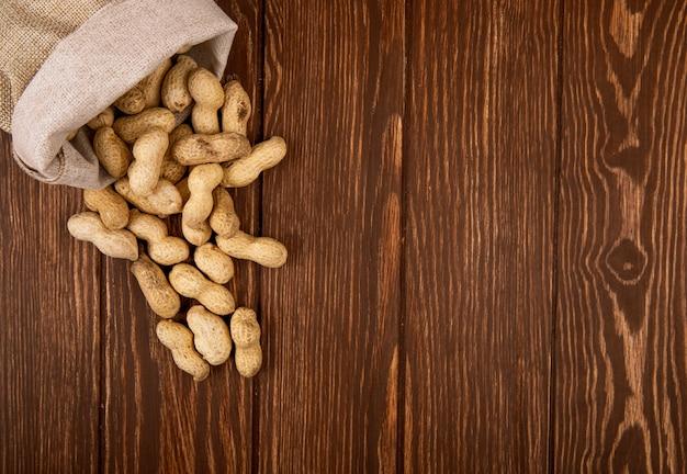 Odgórny widok arachidy w skorupie rozpraszał od worka na drewnianym tle z kopii przestrzenią