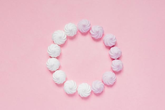 Odgórny widok białe i różowe kręcone bezy na różowym tle