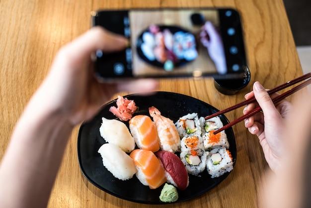 Odgórny widok bierze fotografię suszi na stole kobieta