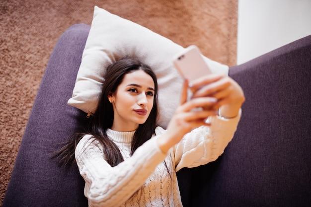 Odgórny widok bierze selfie z jej mądrze telefonem w domu przy białą poduszką piękna brunetka