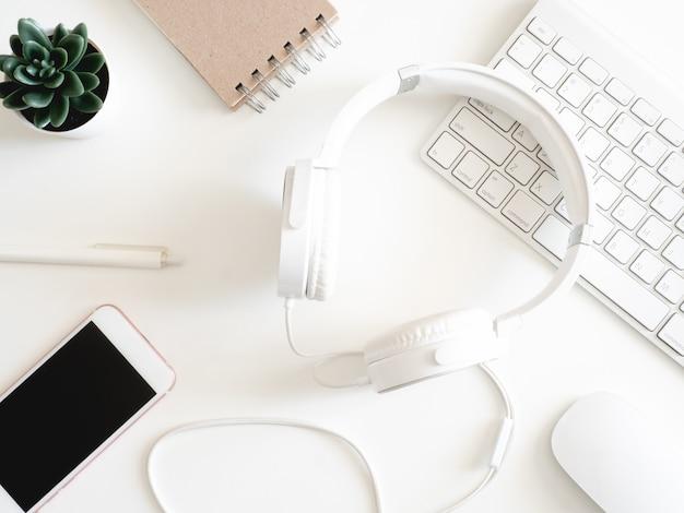 Odgórny widok biurowego biurka workspace z notatnikiem, smartphone i gadżetem na białym tle