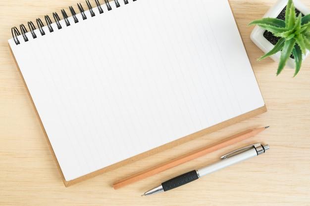 Odgórny widok biurowy biurko z otwartym ślimakowatym notatnikiem na drewno stole