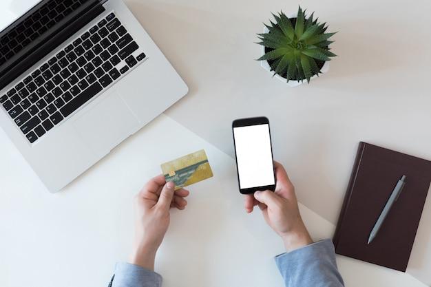 Odgórny widok biznesmena biurowy biurko z kartą kredytową dla online zapłaty na laptopie lub telefonie komórkowym, mieszkanie nieatutowy