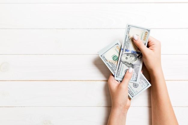 Odgórny widok bizneswomanu ręki liczy sto dolarowych banknotów na drewnianym tle. sukcesu i bogactwa pojęcie z kopii przestrzenią