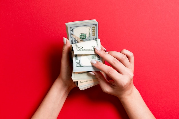 Odgórny widok bizneswomanu ręki liczy sto i różnych dolarowych banknotów na kolorowym tle. koncepcja sukcesu i bogactwa