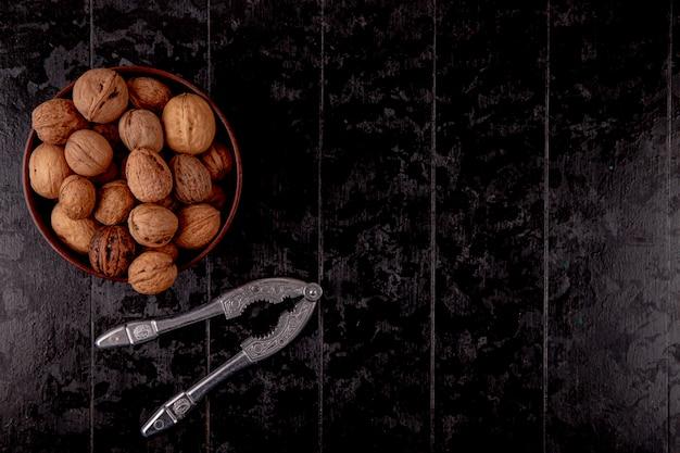 Odgórny widok cali orzechy włoscy w drewnianym pucharze na czarnym tle z kopii przestrzenią