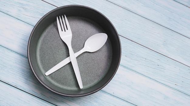 Odgórny widok ceramiczny round naczynie talerz i cutlery ustawia odosobnionego na drewnianym stole z kopii przestrzenią.