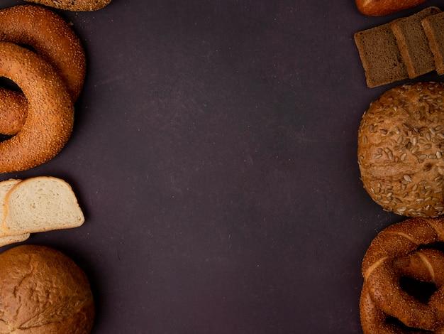 Odgórny widok chleby jako bagel klasyk i oziarniony cob bagel biały i żyto chleba plasterki na bordowym tle z kopii przestrzenią