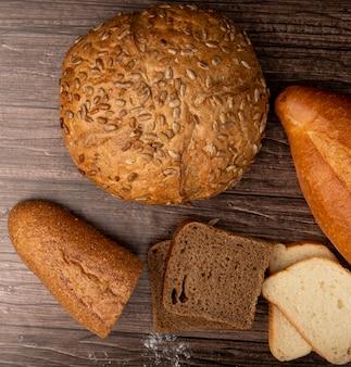 Odgórny widok chleby jako brown ziarnowy cob baguette żyto i biel ones na drewnianym tle