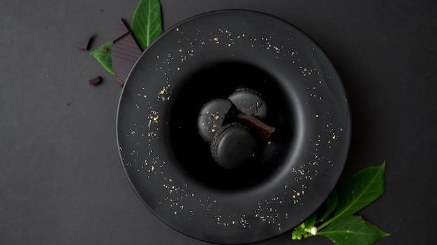 Odgórny widok ciemnej czekolady macarons na czarnym talerzu na zmroku stole