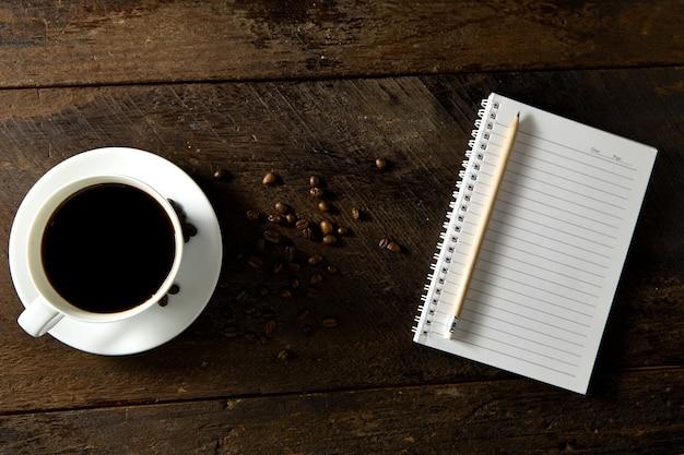 Odgórny widok czarna kawa i pusty notatnik