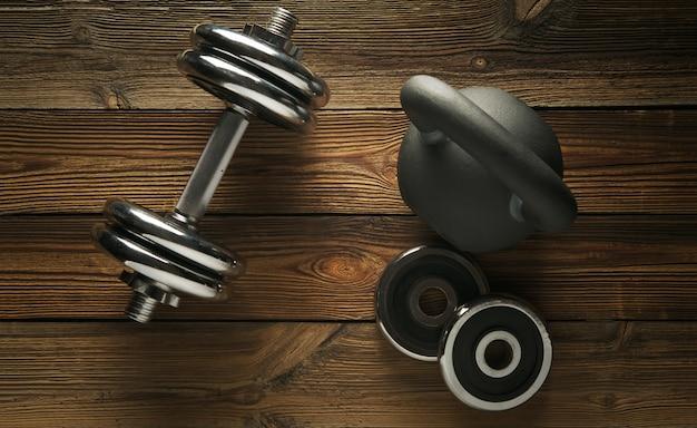 Odgórny widok czerni żelaza kettlebell, dumbbell na drewnianej podłoga