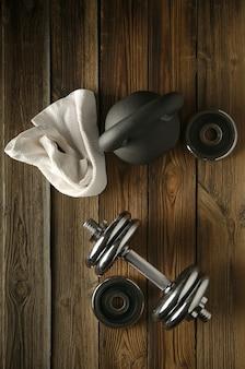 Odgórny widok czerni żelazny kettlebell, dumbbell i biały ręcznik na drewnianej podłoga w gym