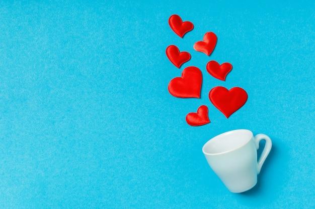 Odgórny widok czerwoni tekstylni serca bryzga z filiżanki na stole.