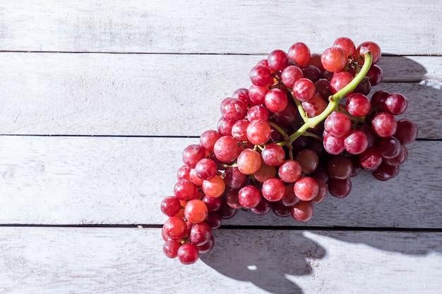 Odgórny widok czerwoni winogrona na drewnianym stole. wolne miejsce na tekst