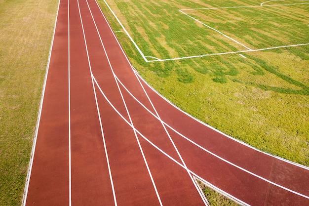 Odgórny widok czerwony bieg ślada i zielonej trawy gazon. infrastruktura do uprawiania sportów.