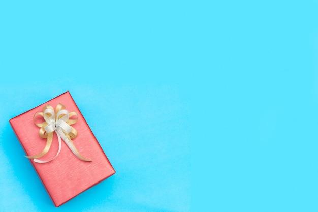 Odgórny widok czerwony prezenta pudełko z łęku dekolacją na błękitnym tle