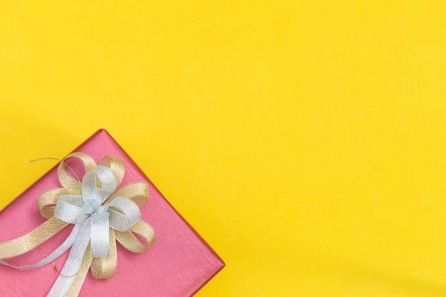 Odgórny widok czerwony prezenta pudełko z łęku dekolacją na żółtym tle