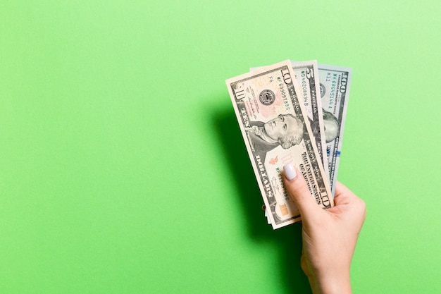 Odgórny widok daje różnorodnym dolarowym rachunkom na kolorowym tle żeńska ręka