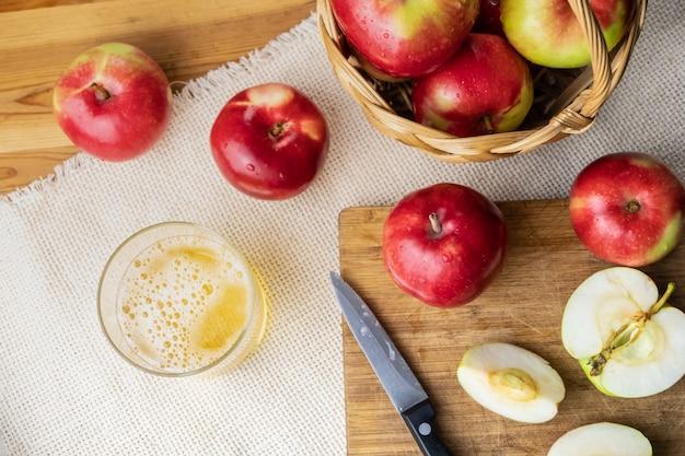 Odgórny widok dojrzali soczyści jabłka i szkło cidre pijemy na nieociosanym drewnianym stole. szklanka domowego jabłecznika i lokalnie uprawianych jabłek ekologicznych, wystrzelona z góry