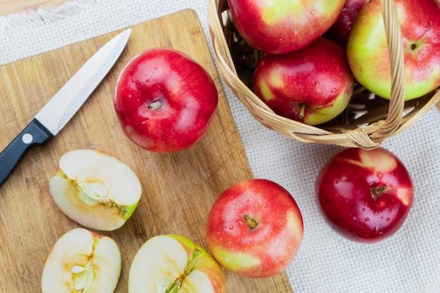 Odgórny widok dojrzali soczyści jabłka na nieociosanym drewnianym stole. domowe organiczne jabłka i nóż, zastrzelony z góry