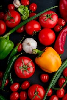 Odgórny widok dojrzałych świeżych warzyw kolorowych dzwonkowych pieprzy pomidorów czosnku brokuły i zielona cebula na czarnym tle