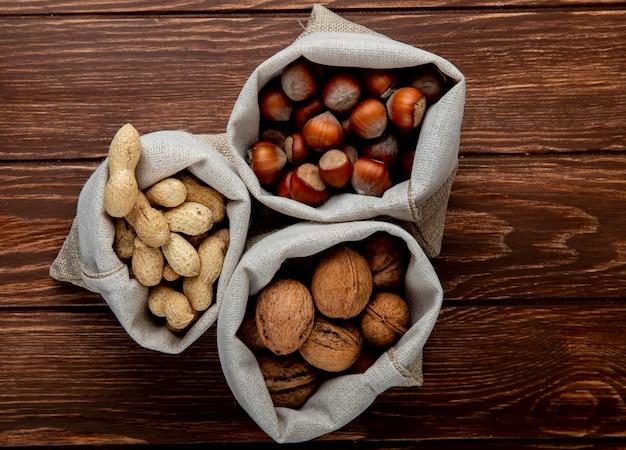 Odgórny widok dokrętki w worków orzechów włoskich arachidach i hazelnuts w skorupie na drewnianym tle