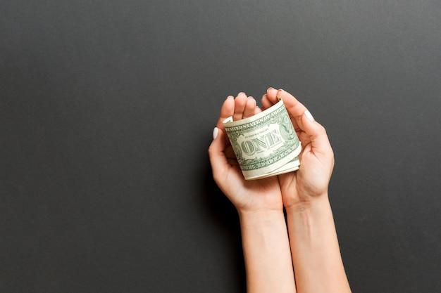 Odgórny widok dolarowi banknoty w kobiet rękach na kolorowym tle. koncepcja emerytury i ubóstwa