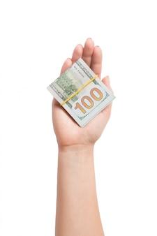 Odgórny widok dolarowi rachunki w tubkach w żeńskiej ręce na białym odosobnionym tle