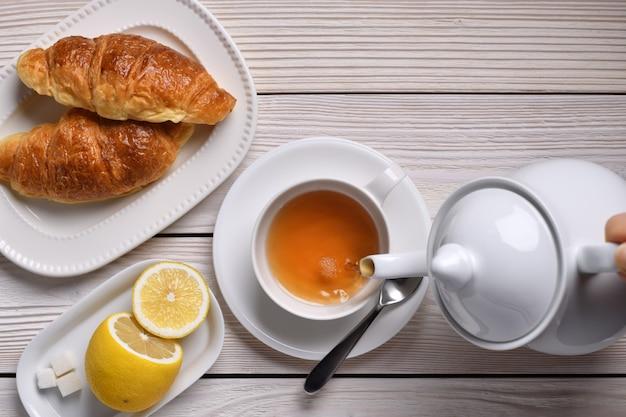 Odgórny widok dolewanie herbata na filiżance z cytryną i croissants na bielu stole