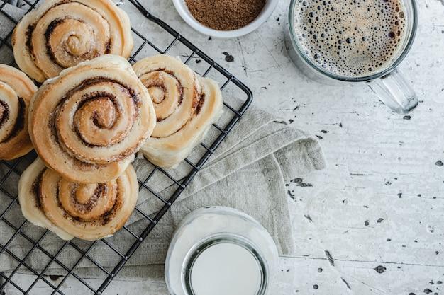 Odgórny widok domowej roboty cynamonowe rolki na grillu danishes i amerykańska kawa w szklanej filiżance.