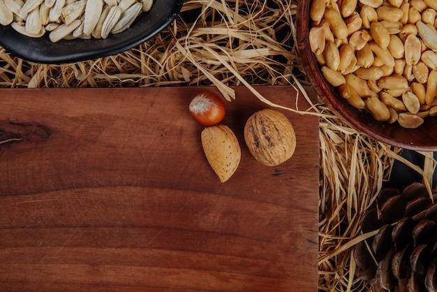 Odgórny widok drewniana deska z dokrętkami i piwem przekąsza na słomie