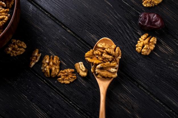 Odgórny widok drewniana łyżka z orzechami włoskimi i cukierki wysuszonymi daktylowymi owoc na drewnianym